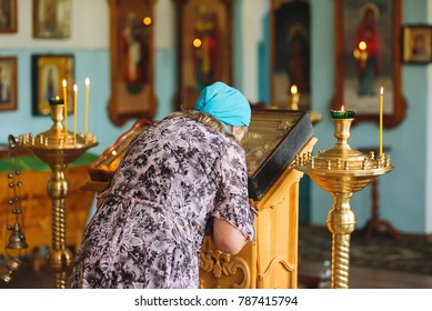 a woman prays in church and kisses an icon