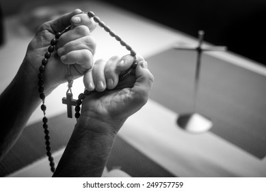 A woman prays to God. In the background holy bible and rosary. Black and white