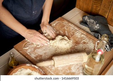 Woman prepares dough on pastry board with flour and rolling pin on white wooden table