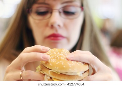 Woman prepares for eating hamburger in cafe, focus on hamburger, shallow dof