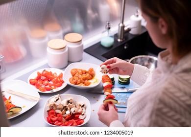 Woman prepares meat and vegetable skewers.