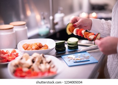 Woman prepares meat and vegetable skewers.