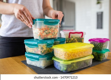 Woman preparing containers with frozen mixed vegetables for freezer.