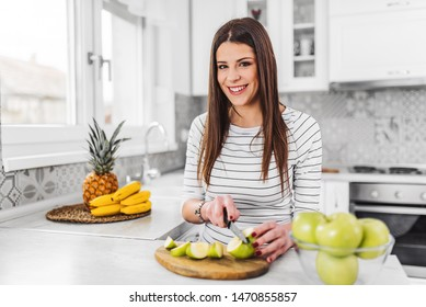 Woman preparing a delicious vegan snack in her kitchen with fruit, she is slicing an organic green apple using a cutter