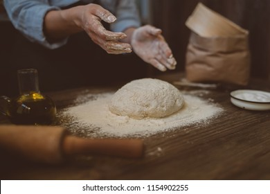 Woman preparing dough at table in bakery for bread or pizza on a rustic wooden surface with natural light. Sprinkling flour over fresh dough on kitchen table. Selective focus. Toned image.