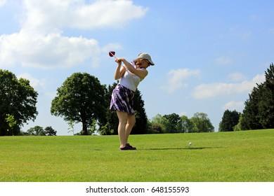 Woman Preparing To Drive Golf Ball Down The Fairway Towards The Green.