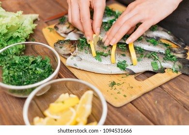 Woman preparing fish trout with lemons and greenery on wooden table, view of hands.