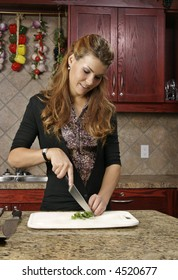 Woman preparing food using fresh sliced basil for a meal.