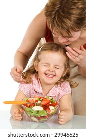 Woman preparing fruit salad to her little happy laughing girl - isolated