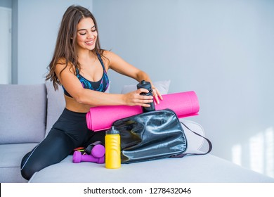 Woman preparing gym bag for all day. Preparing gym bag at home. Young woman packing sports stuff for training into bag in living room. Space for text. Woman preparing gym bag for active day.