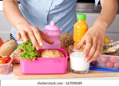 Woman preparing healthy breakfast for school in the kitchen