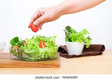 Woman preparing healthy salad, adding tomato cherry to the bowl.