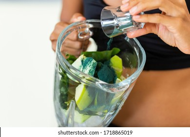 Woman preparing an inmunne boosting  green juice with apple, spirulina, cucumber, celery and spinach.