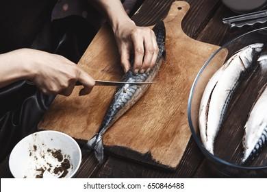 Woman preparing mackerel fish