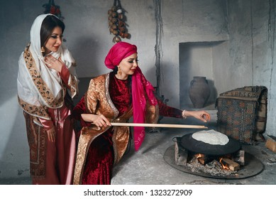 Woman preparing or making borek or bread dough. Girl friends keep rolling pin on dough with flour. Cooking traditional Turkish borek, pide, pita or yufka bread. Traditional Turkish food