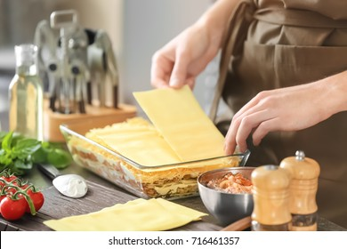 Woman preparing meat lasagna in kitchen
