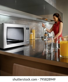 woman preparing orange juice and a microwave oven copia
