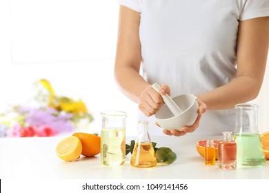 Woman preparing perfume oil at table indoors