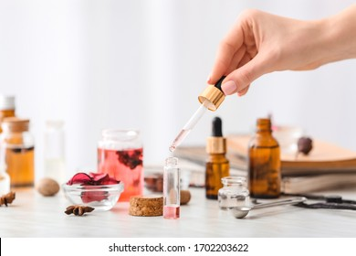 Woman preparing perfume on table
