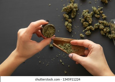 Woman preparing and rolling marijuana cannabis joint. Marijuana use concept. Woman rolling a marijuana joint. Close up of marijuana blunt with grinder.
