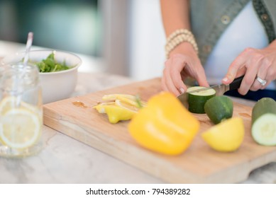 woman preparing salad with fresh vegetables