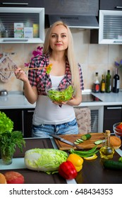 Woman preparing salad at the kitchen table with vegetables - Portrait of the beautiful girl near kitchen table