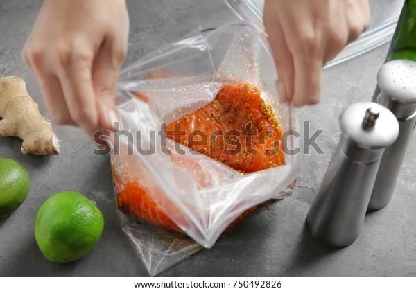 テーブルの上のジップロックバッグにハニーマスタードマリネードを入れ、サケのすみ肉を作る女性