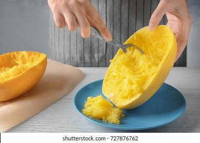 Woman preparing spaghetti squash in kitchen