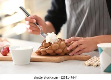Woman preparing sweet bubble waffles in kitchen
