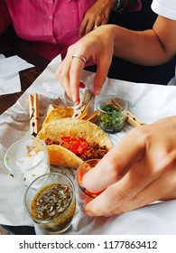 Woman preparing a taco to eat inside a restaurant.