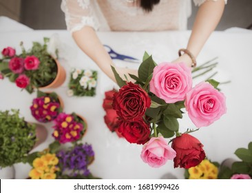 Woman Preparing to trim red and pink roses and beautiful flower arrangements in the home, flower arrangements with vase for gift-giving for Valentine's Day and Business in the family on the on table