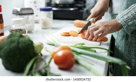 woman preparing vegetables for healthy meal and salad in a kitchen