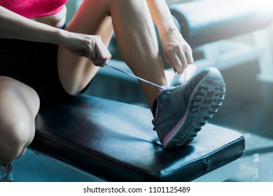 woman preparing to workout with sneaker putting on bench in gym