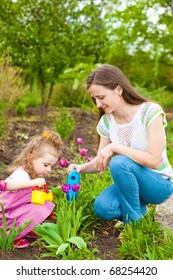 Woman with preschool girl watering flowers in  garden