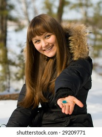 woman presentate blue pill in winter forest