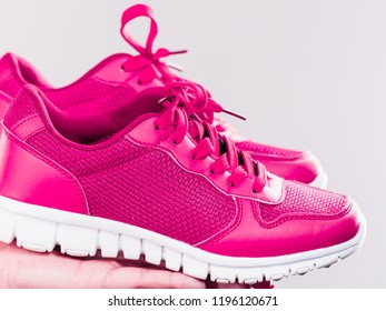 Woman presenting sportswear trainers red shoes, comfortable footwear perfect for workout and training.