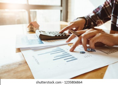 Woman press the calculator to calculating financial chart for investment to buying property.