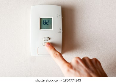 A woman is pressing the down button of a wall attached house thermostat with digital display showing the temperature. A concept image for electricity bill, heating, cooling, eco friendly, saving etc.