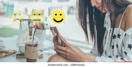 woman pressing face emoticon on virtual touch screen at smartphone .Customer service evaluation concept.
