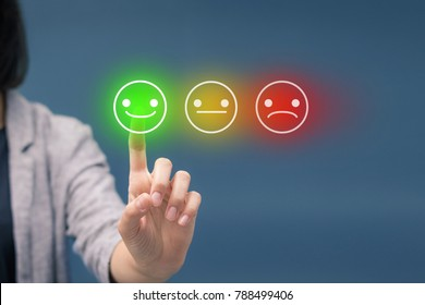 Woman pressing happy smiley face emoticon on virtual touch screen. Customer service evaluation and rating concept.