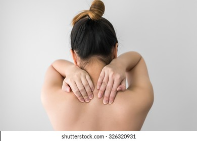 Woman pressing her hand on painful shoulder. Pain in the human body