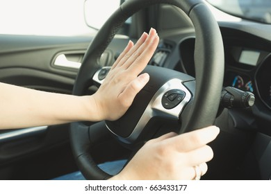 Woman pressing honk button on steering wheel
