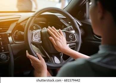 Woman pressing the horn while driving a car through the road.