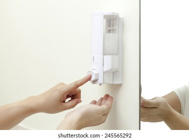 woman pressing the liquid soap to her hand