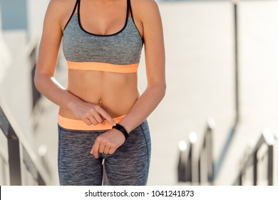 Woman pressing on smart band. Slim female body and toned abdominal muscles. Fitnes and using smart devices concept.