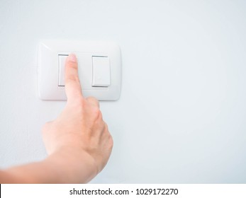 Woman is pressing the switch button for turning on the light.