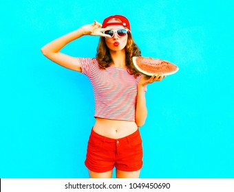 Woman pretty  is holding a slice of watermelon over a colorful blue background wearing a red baseball cap