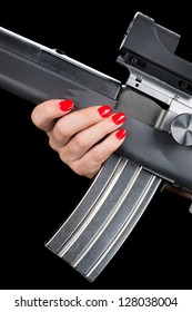 A woman with pretty red painted fingernails holds onto an assault rifle with a fully loaded magazine.