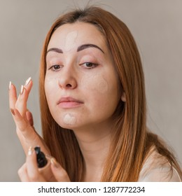 Woman with problem skin prone to rashes and acne, acne scars put on make up concealer and foundation , concept of healthy skin, dermatology and cosmetology