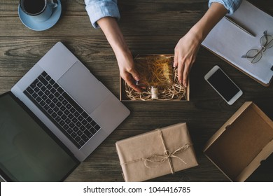 Woman with product packaging work at home concept, small and medium-sized enterprises (SMEs) concept. Girl is freelancer with her private business at home office, working with laptop, coffee cup.